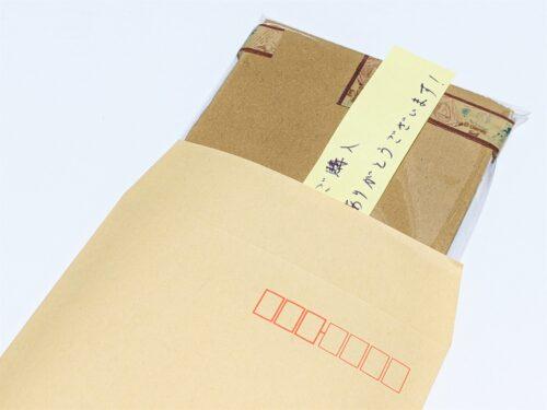梱包したギフト券を封筒に入れる